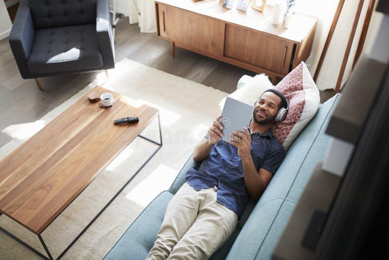 Man som ligger på Sofa At Home Wearing Headphones och hållande ögonen på film på den Digital minnestavlan royaltyfri foto
