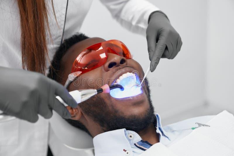 Man som ligger på tandläkarestol i skyddande exponeringsglas i klinik royaltyfri bild