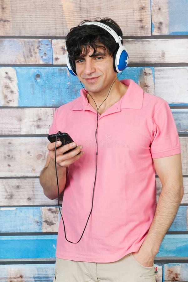 Man som lyssnar till musik med den smarta telefonen royaltyfri foto