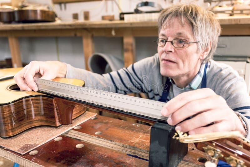 Man som mäter grinigheterna på en gitarr arkivfoton