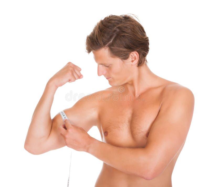 Man som mäter hans biceps arkivbild