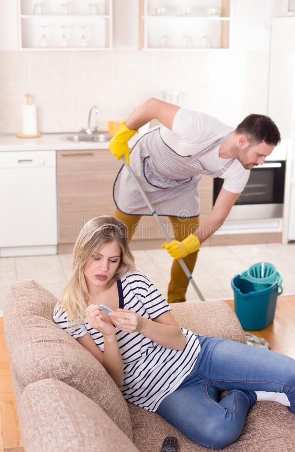 Man som moppar golvet medan kvinna som vilar på soffan royaltyfria foton
