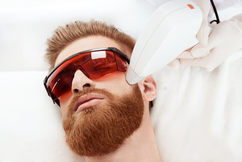 Man som mottar laser-hudomsorg på framsida sunt livsstilmanbegrepp arkivfoton