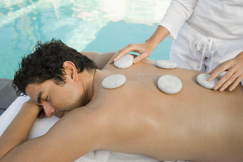 Man som mottar varm stenmassage vid pölen royaltyfri foto