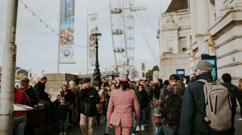 Man som mycket bär en dräkt av Storbritannien flaggor, medan gå mellan folkmassan i London, Förenade kungariket arkivfoto