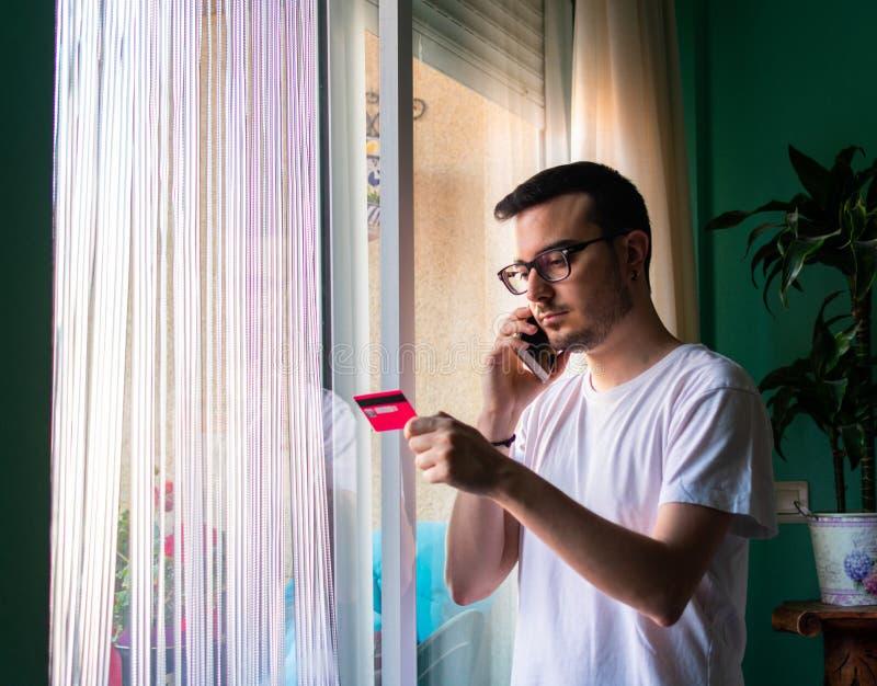 Man som nästan betalar med en kreditkort med mobilen fönstret arkivfoto