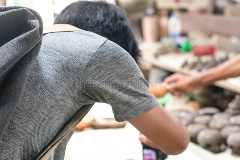 Man som ner böjer för att ta ett foto av thailändsk krukmakeri royaltyfria foton