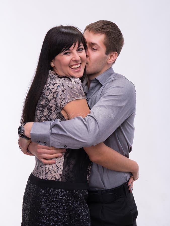 Man som kysser hans le flickvän arkivbild