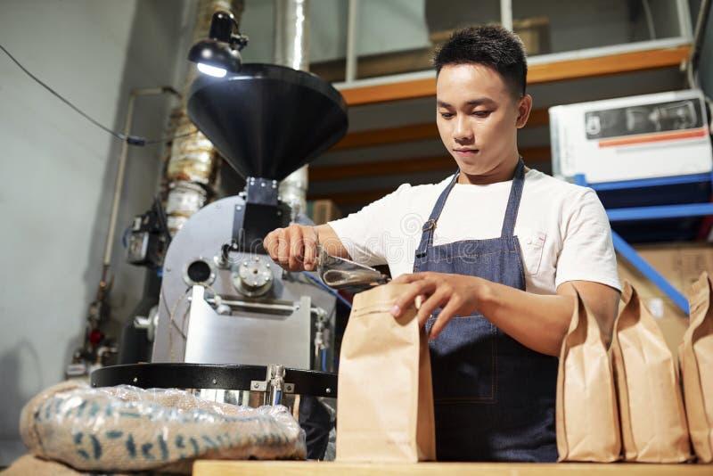 Man som packar kvalitets- kaffekorn i p?se royaltyfria foton