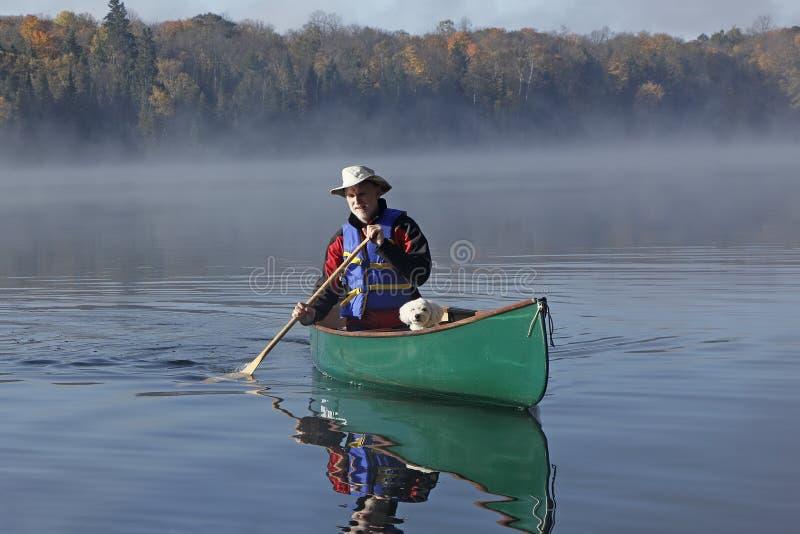 Man som paddlar en kanot med en liten vit hund i pilbågen royaltyfria foton