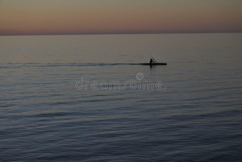 Man som paddlar i kajak med dramatisk solnedgång royaltyfri fotografi
