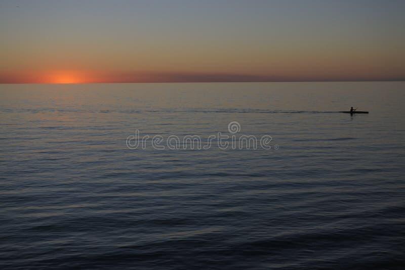 Man som paddlar i kajak med dramatisk solnedg?ng arkivbilder