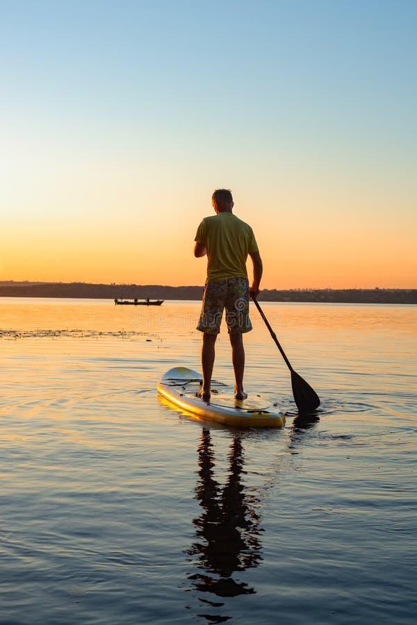 Man som paddlar på ett SUPbräde under soluppgång royaltyfri foto