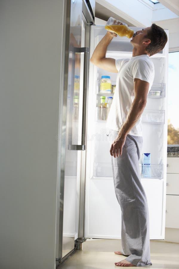 Man som plundrar kylen för drink på natten arkivfoto