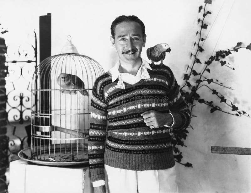 Man som poserar med älsklings- fåglar (alla visade personer inte är längre uppehälle, och inget gods finns Leverantörgarantier at royaltyfri bild