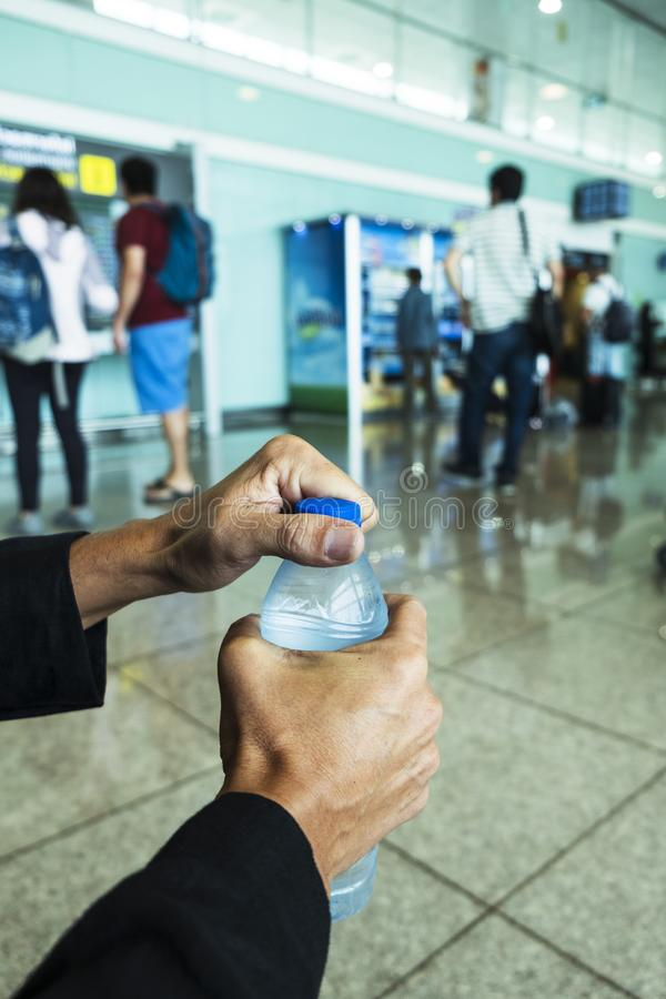 Man som ?ppnar en vattenflaska i en station eller en flygplats royaltyfria bilder