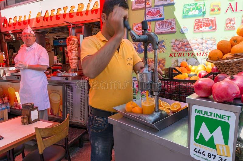 Man som pressar apelsiner in i orange fruktsaft genom att använda pressmaskinen royaltyfri bild