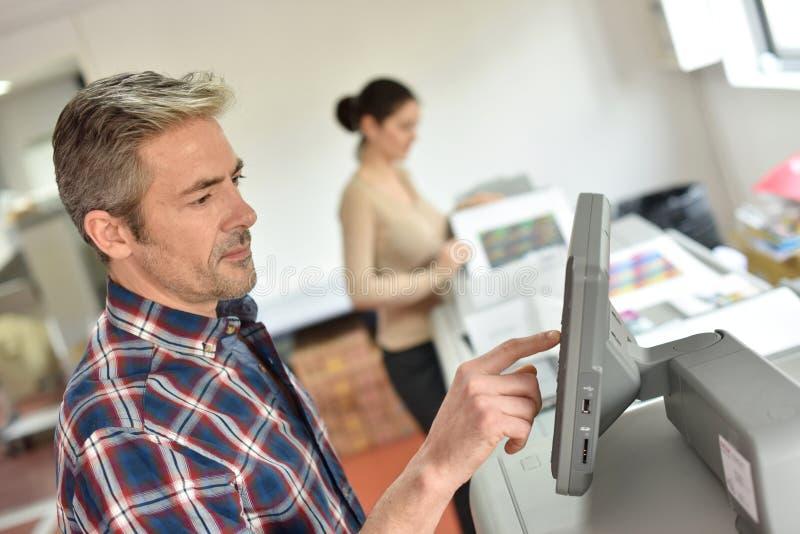 Man som programmerar printingmaskinen med lärlingen royaltyfria foton