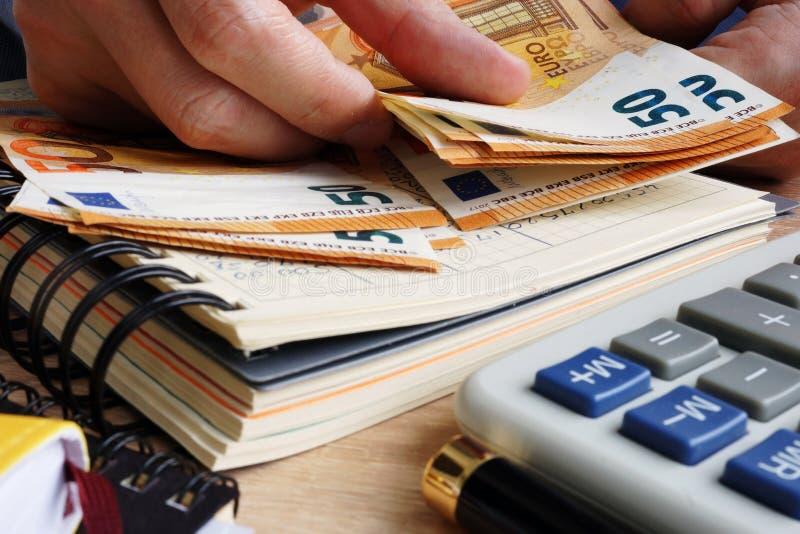 Man som räknar eurosedlar Skrivbord med räknemaskinen, huvudboken och euro royaltyfria foton