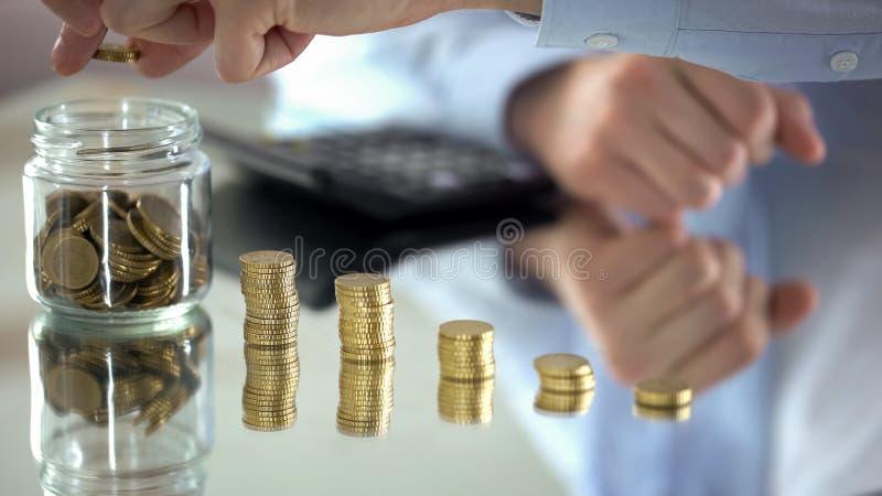 Man som räknar mynt, förhöjning av inkomst, finansiellt pyramidbegrepp, investering royaltyfri bild