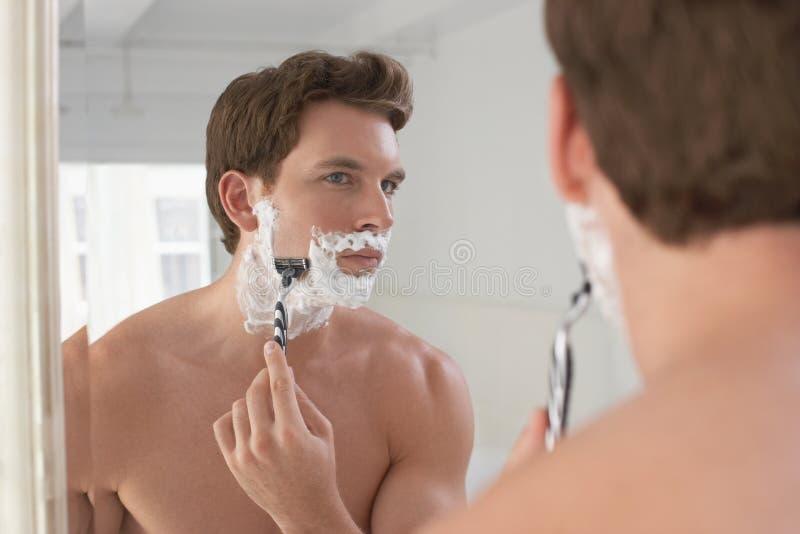 Man som rakar i badrumspegel royaltyfri bild