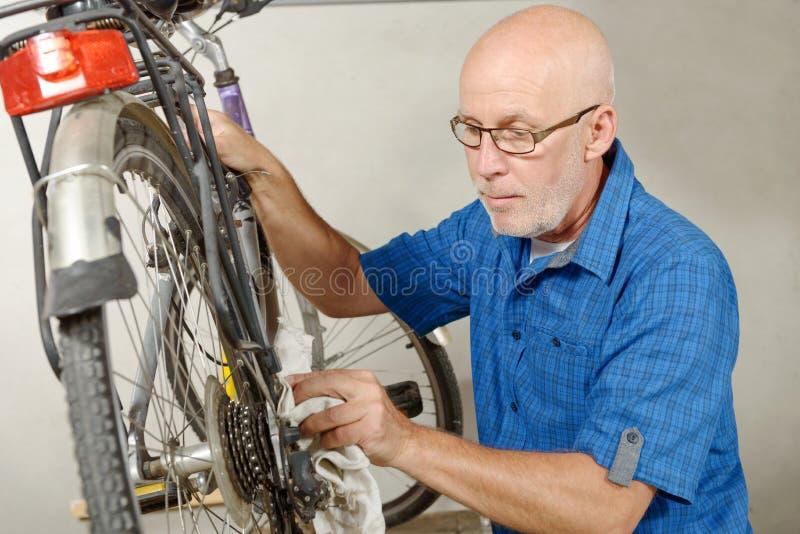Man som reparerar cykeln i hans seminarium arkivfoto