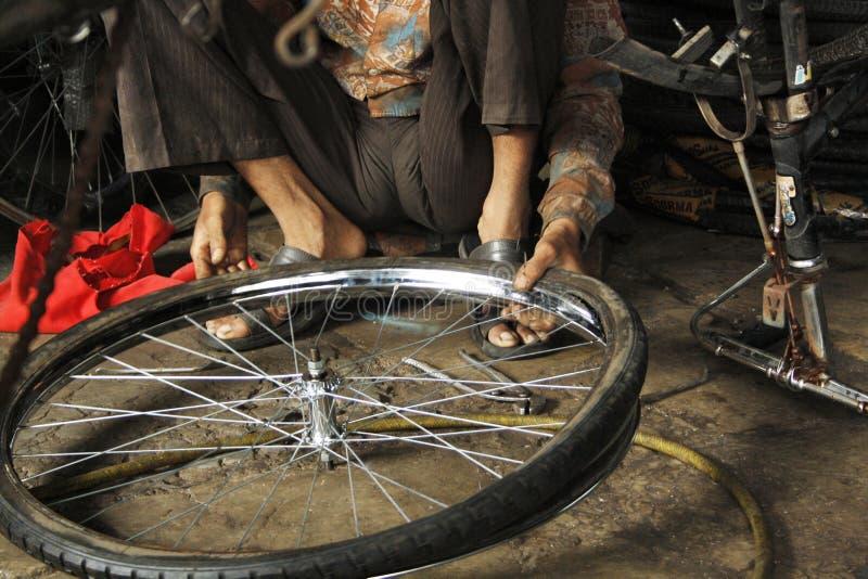 Man som reparerar cykeln på den Ratan cirkuleringsmarknaden, Mandai, Pune, Indien royaltyfri foto