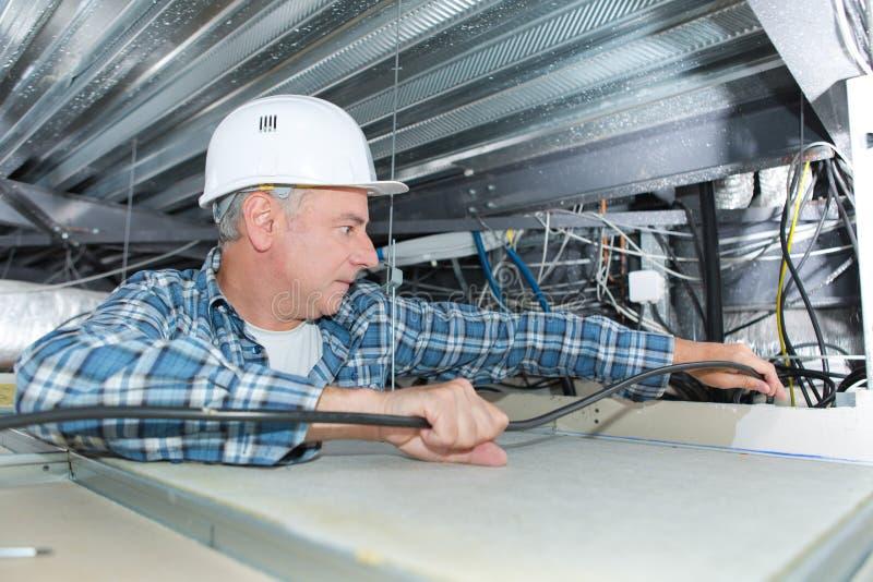 Man som reparerar elektriskt ledningsnät på tak arkivfoton