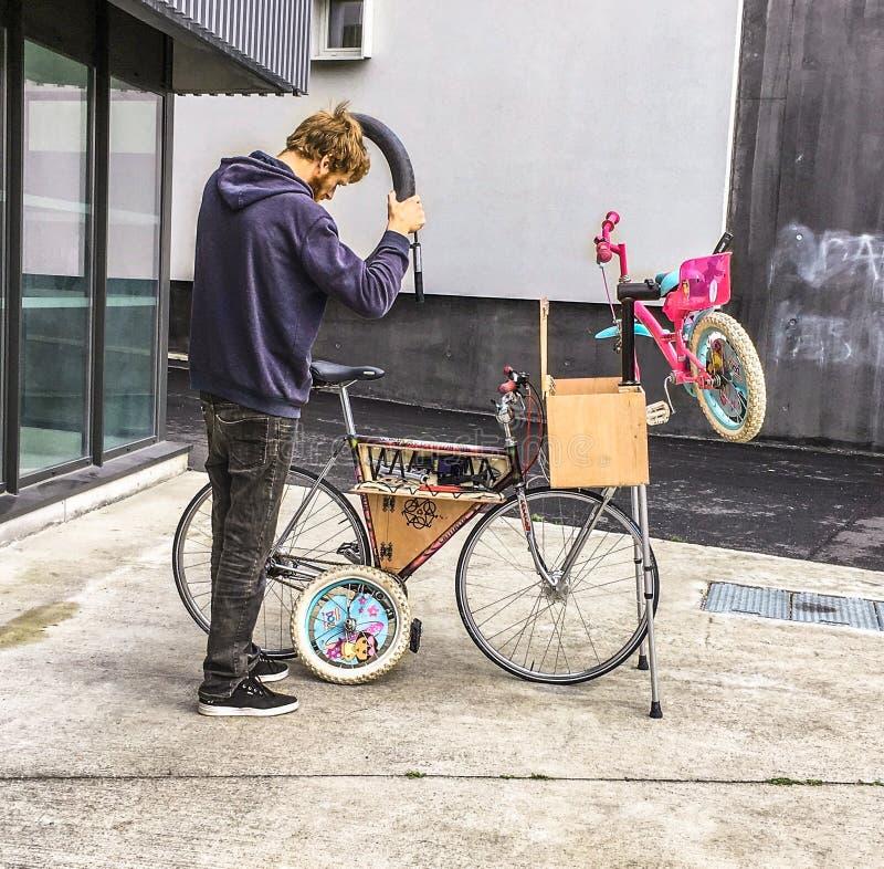 Man som reparerar ett barns cykel på en mobil cykelreparationsenhet royaltyfri foto