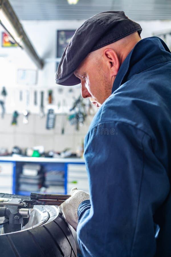 Man som reparerar motorcykelgummihjulet med reparationssatsen, sats för gummihjulproppreparation för slanglösa gummihjul royaltyfri foto