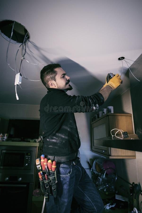 Man som reparerar och installerar elektricitet royaltyfri bild