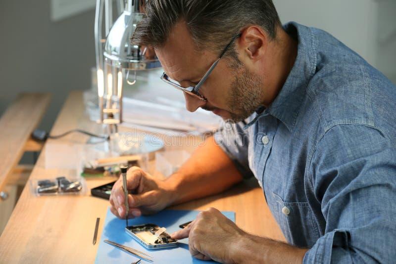 Man som reparerar smartphonen i seminarium royaltyfri foto