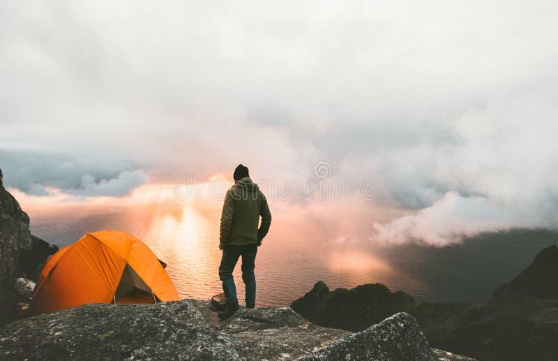 Man som reser med tältet som campar på bergöverkant fotografering för bildbyråer