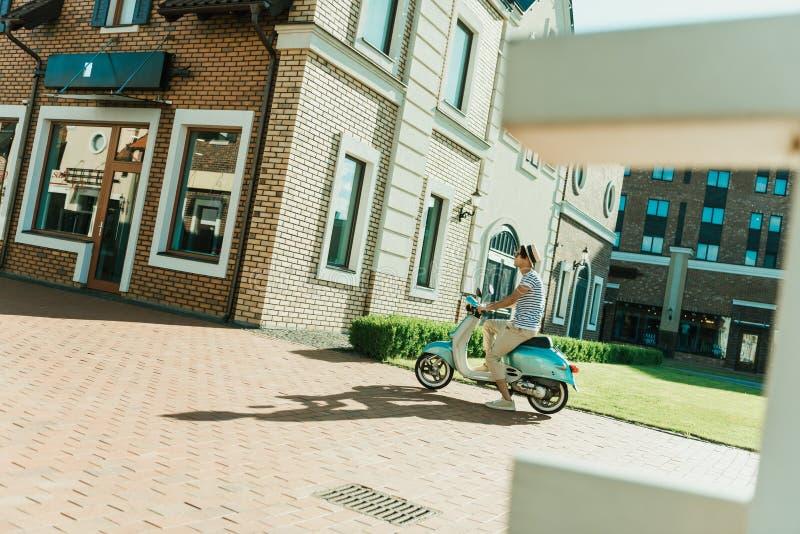 Man som rider den retro sparkcykeln på gatan arkivbilder