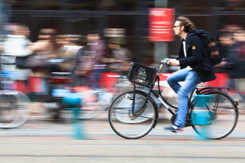 Man som rider en cykel ner gatan. Amsterdam arkivbilder