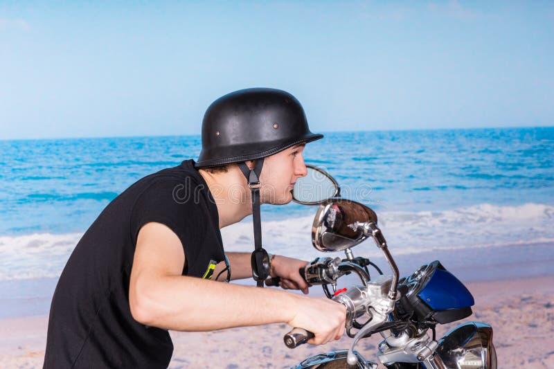 Man som rider en motorcykel på stranden med hjälmen arkivbilder