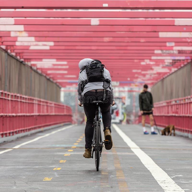 Man som rider hans cykel i den cykla gränden på den Williamsburg bron, Brooklyn, New York City fotografering för bildbyråer