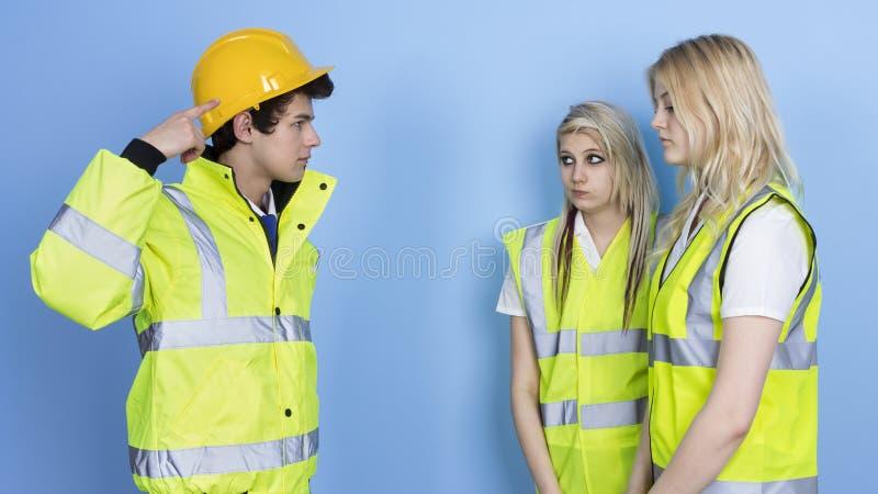 Man som ropar till den kvinnliga arbetaren för att inte bära den hårda hatten royaltyfri foto