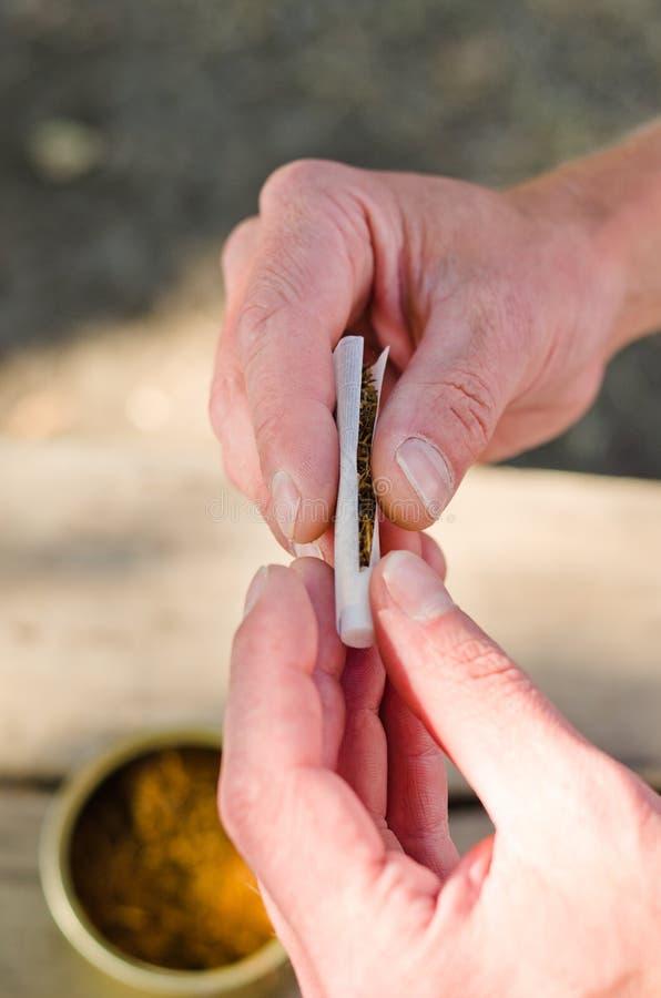 Man som rullar en cigarett royaltyfria foton