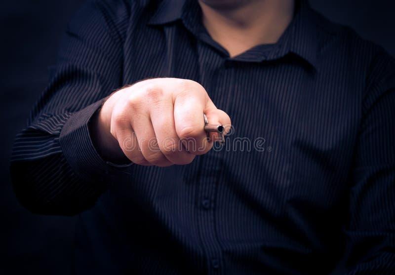 Man som rymmer den gamla nyckel- handen royaltyfri foto