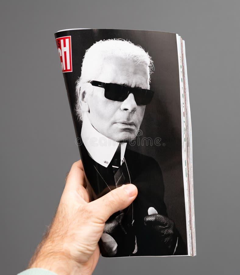 Man som rymmer den Paris Match tidskriften fransk med den Karl Lagerfeld ståenden royaltyfria foton