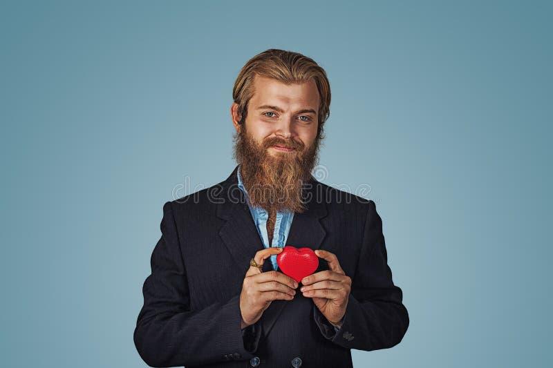 Man som rymmer den röd stor hjärta formade gåvaasken arkivfoto