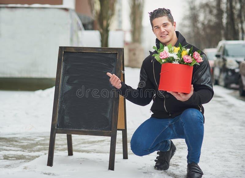 man som rymmer den röda gåvaasken med den härliga buketten av att blomma rosa, gula och vita tulpan och vita krysantemum med gräs arkivfoton