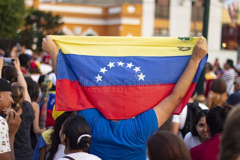 Man som rymmer den venezuelanska flaggan på protesten mot Nicolas Maduro arkivbild