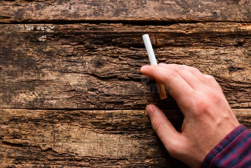 Man som rymmer en cigarett i hans hand royaltyfri foto
