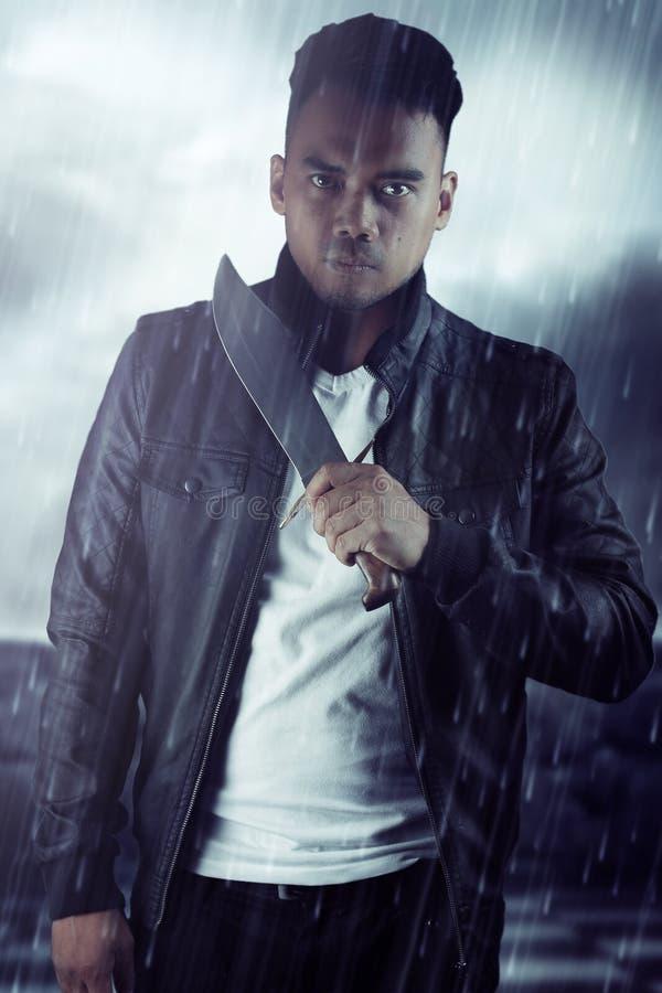 Man som rymmer en kniv i regnet Bokomslagdesign fotografering för bildbyråer