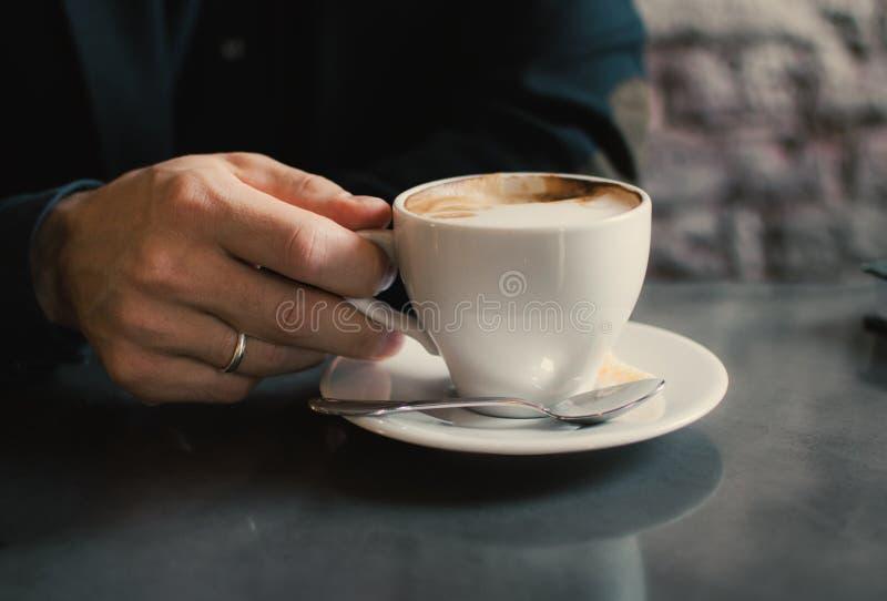 Man som rymmer en kopp av cappuccino fotografering för bildbyråer