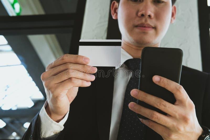 Man som rymmer en kreditkort och använder den smarta telefonen för online-shopp royaltyfri fotografi