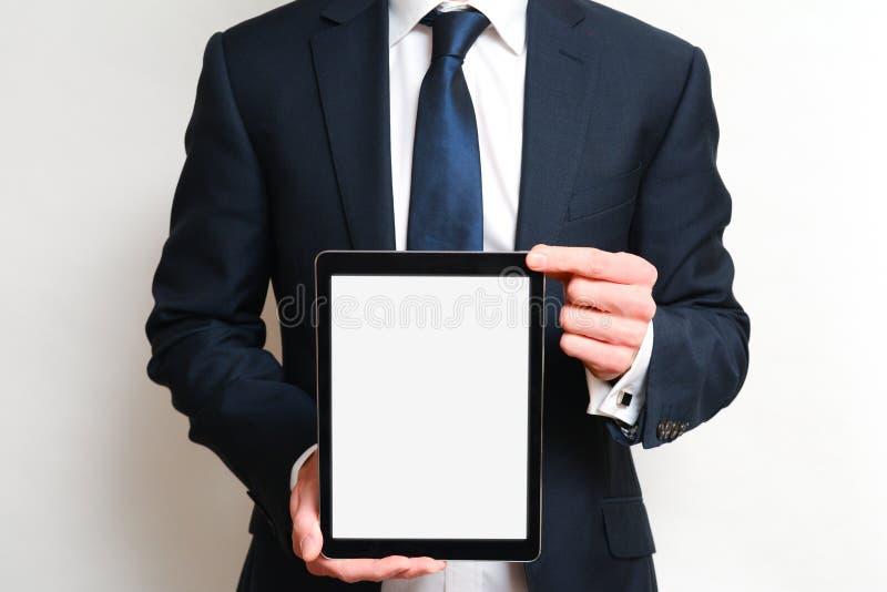Man som rymmer en minnestavlaapparat med den tomma vita skärmen som bär en affärsdräkt royaltyfria foton
