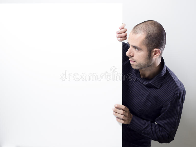 Man som rymmer en vit affischtavla. royaltyfria bilder